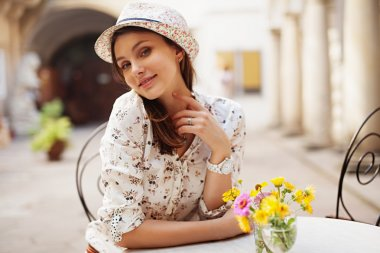 girl sitting at a table in a hat