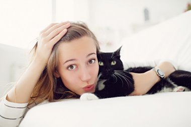 girl with  cat lying on the bed