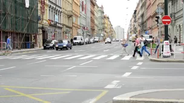 městské ulice s předáním aut a přechod pro chodce: lidí, kteří jdou - budovy v městě v pozadí - timelapse