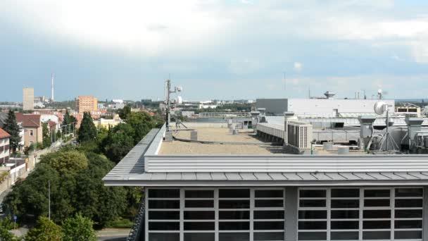 střecha budovy - klimatizace a další zařízení (strojovny) - město (budovy v pozadí) s přírodou - zamračená obloha