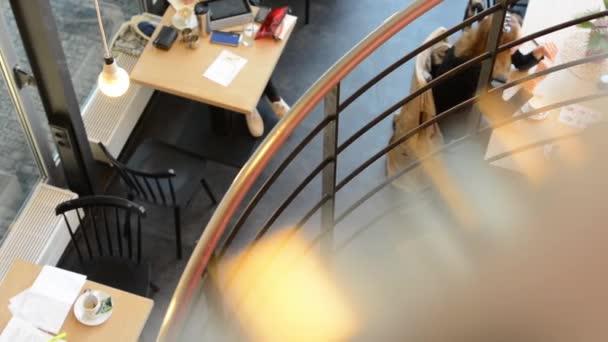 mladá žena jde po schodech nahoru - ostatní lidé sedí dole a mluvit a pít kávu