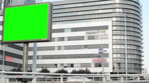 Billboard ve městě poblíž silnice - zelené obrazovky - budovy v pozadí - auta