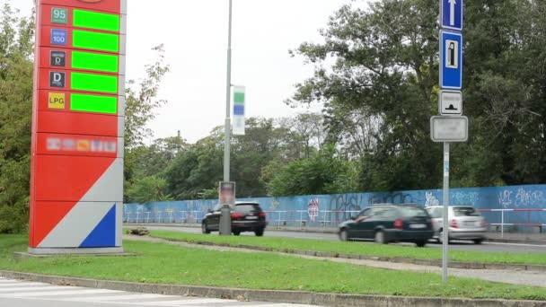 palivové stanice - projíždějících aut - stromy a trávu - informační panel s cenami pohonných hmot - zelená obrazovka