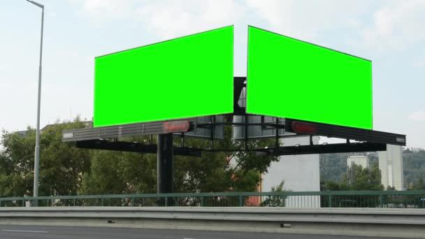 dva billboardy v městě poblíž silnice - zelené obrazovky - budovy v pozadí - auta