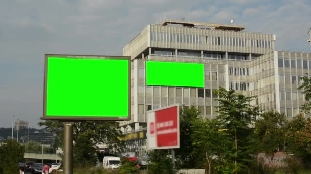 Two billboards in the city near road (on the building) - green screen - building and passing cars - nature (trees)