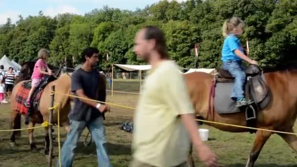 Atrakce na výstavě - děti jezdí na koně - stánky - lesní (stromy