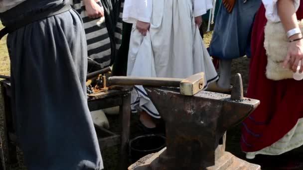 Kovářské nástroje - kladivo a kovadlina a další - lidé kolem