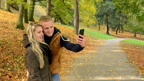 Young model couple in love - autumn park(nature) - man and woman are photographing  by smartphone (selfie) - happy couple