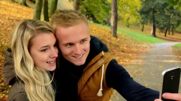 Young model couple in love - autumn park(nature) - man and woman are photographing  by smartphone (selfie) - happy couple - couple kiss