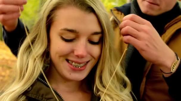 Fiatal modell pár a szerelem - őszi park(nature) - az ember ad egy ajándék, hogy nő - boldog pár - ember ad egy nő egy nyaklánc