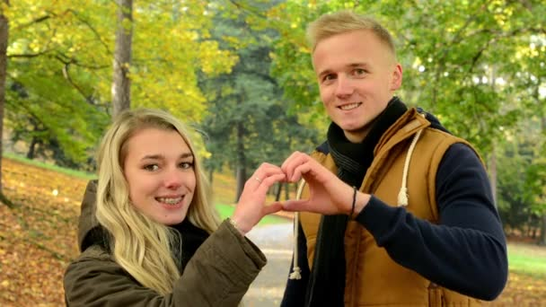 Young model couple in love - autumn park(nature) - happy couple - couple forms a heart with their hands - couple kiss - couple embrace