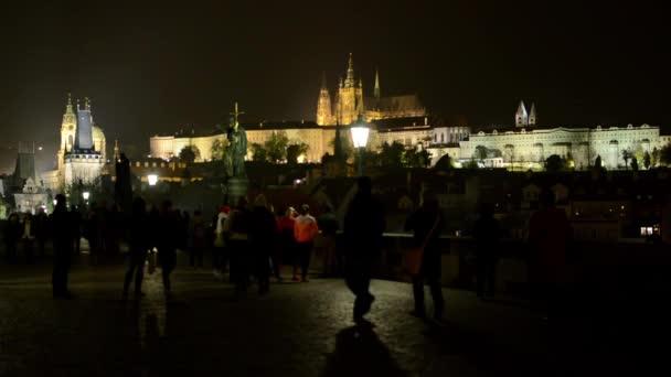 Noční město (budovy) - Karlův most s lidí, kteří jdou - Praha, Česká republika (Hradčany) - Pražský hrad