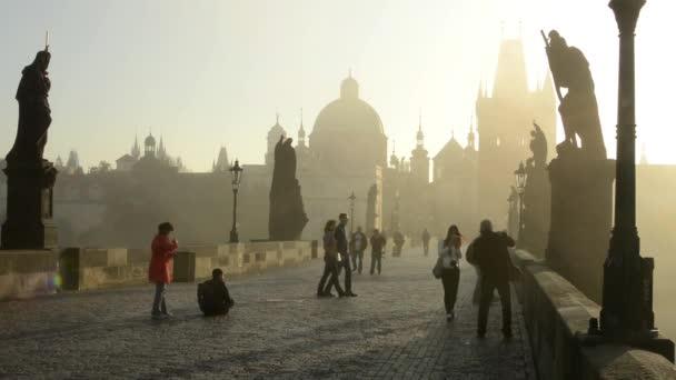 Karlův most s lidmi chodit - sunrise - město - ranní mlha - budovy se sochami - dlážděném chodníku