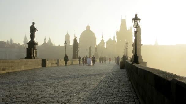 Karlův most s lidmi - sunrise - město - ranní mlha - budovy se sochami