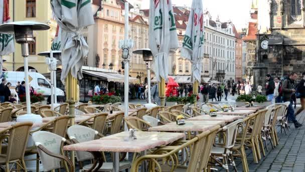 Urban street (město - náměstí) - venkovní restaurace prázdná venkovní posezení (ráno) - lidí, kteří jdou - ročník stavební