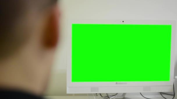 Člověk pracuje na počítači - zelené obrazovky - kancelář - detail