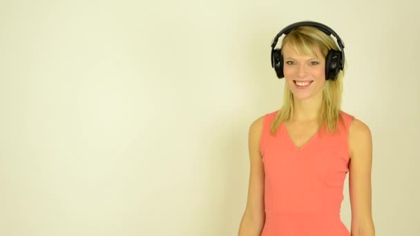 Young attractive woman listens to music with headphones and dancing - studio