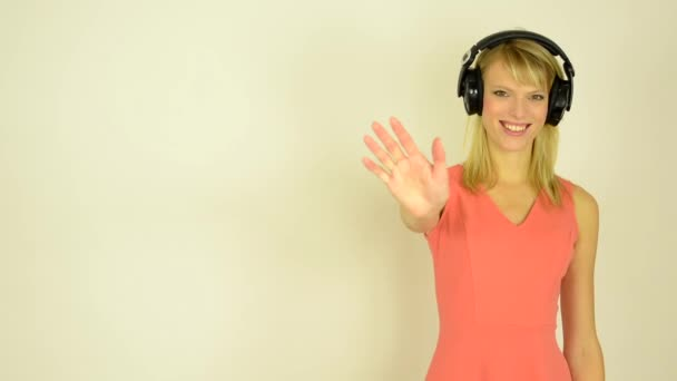 Young attractive woman listens to music with headphones and  waves goodbey with hand - studio