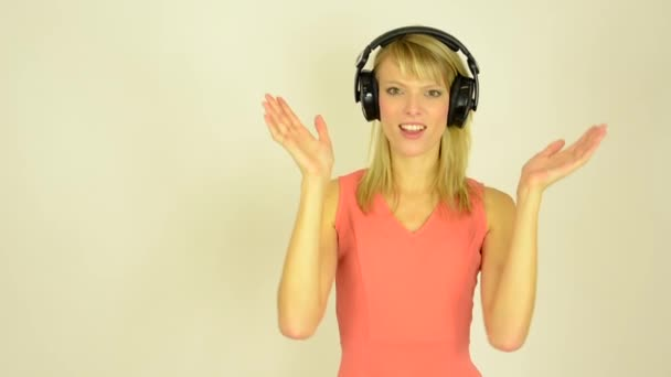 Young attractive woman listens to music with headphones and woman is surprised - studio