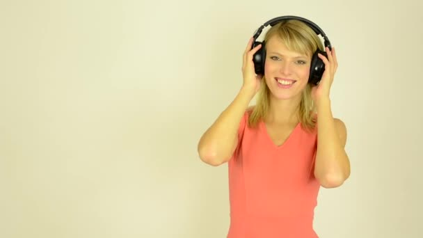 Young attractive woman listens to music with headphones and dancing - studio (hold hands on headphones)