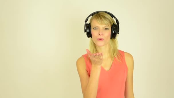 Young attractive woman listens to music with headphones - woman sends mouth to camera - studio