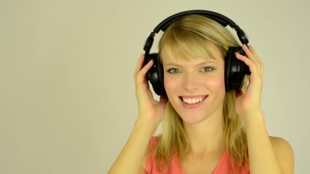 Young attractive woman listens to music with headphones and dancing - studio - closeup (hands hold headphones)