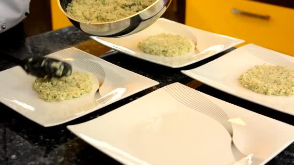 Kuchař připravuje jídla pro servírování - kuchař dá jídlo na desku (rýže)