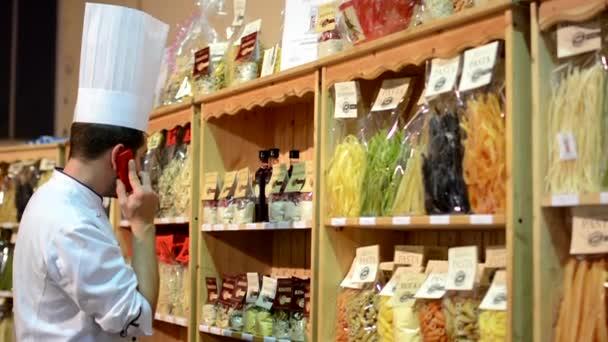 Šéfkuchař telefon před barevné těstoviny (olivový olej, mouku atd.) v pytlích v polici - shop