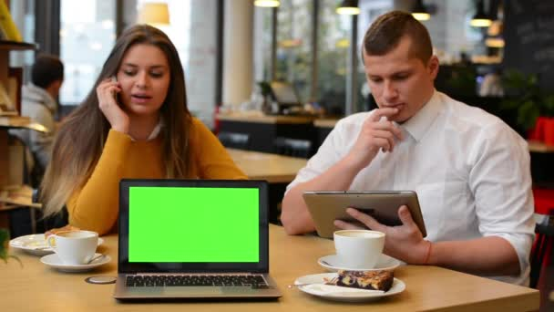 Woman phone and man works on tablet in cafe - coffee and cake - computer green screen (notebook)