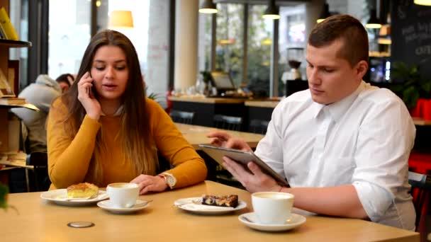 Frau telefoniert und Mann arbeitet im Café am Tablet - Kaffee und Kuchen