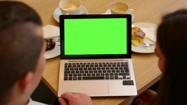 Computer (notebook) green screen - woman and man works on computer in cafe - coffee and cake