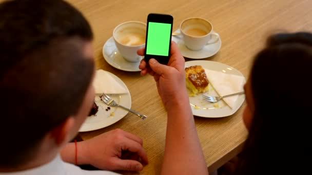 Schermo dello smartphone verde - uomo e donna funziona sul cellulare in caffè - caffè e torta