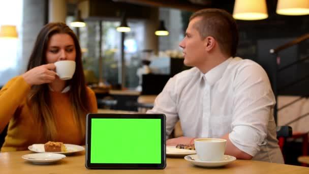 Schermo tablet verde - coppia felice parla, mangia e bere in caffè - caffè e torta