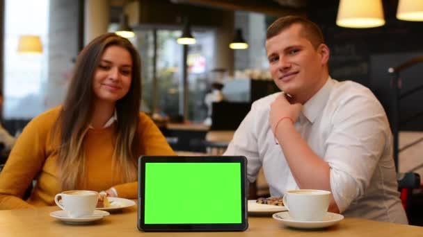 Tableta fabion - šťastný pár úsměvů na kameru a bodu na tabletu v café - káva a koláč