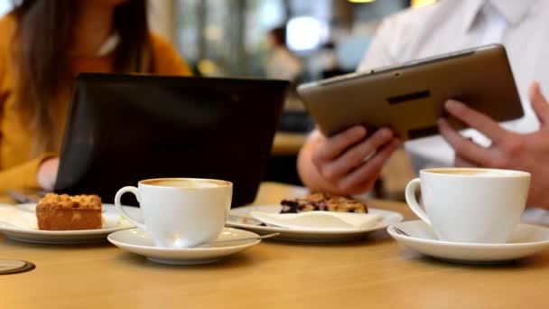 La donna lavora sul computer (notebook) e luomo lavora sul tablet in caffè - caffè e torta - girato sulle mani