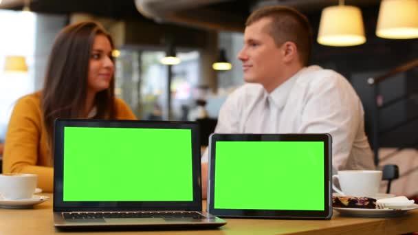 Počítač (notebook) a tablet zelené obrazovky - šťastný pár úsměvů na fotoaparát a poukazují na notebook v café - šťastný pár mluvit - káva a koláč
