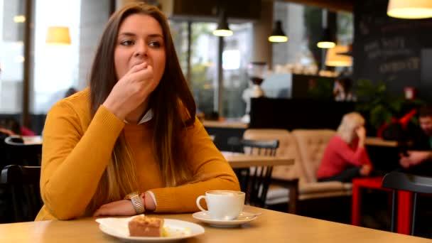 Žena pije kávu a jíst koláče v kavárně