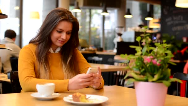 Woman works on smartphone in cafe - coffee and cake