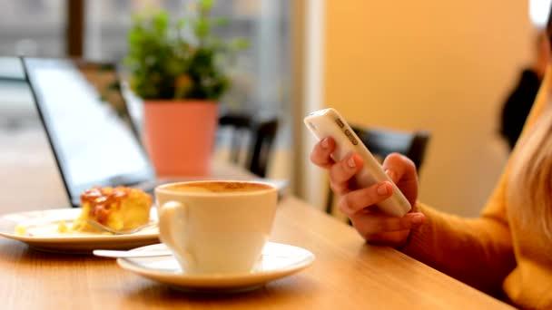 Žena pracuje na smartphone v café - záběr na stranu - počítač, káva a koláč v pozadí - městské ulice s automobily v pozadí
