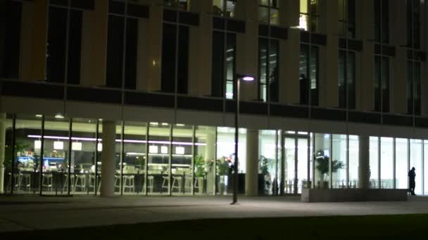 Moderní budova a lidé opustit stavebního úřadu - odvykání čas a vnitřní prázdné restauraci (bar) z mimo - noc