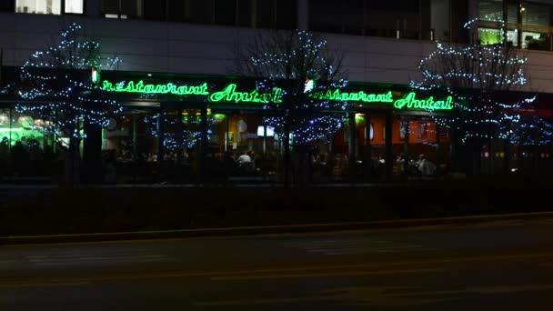 Venkovní restaurace s lidmi - město: městské ulice s automobily - urban stromy zdobí vánoční osvětlení - noc