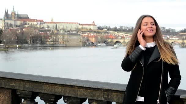 Mladá atraktivní žena telefon na mostě - město (Praha) v pozadí