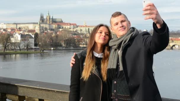 Mladý šťastný pár v lásce na mostě - muž a žena jsou fotografování do smartphone (selfie) - město (Praha) v pozadí