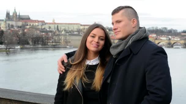 Mladý šťastný pár v lásce polibek a úsměv do kamery - město (Praha) v pozadí - ptáci v pozadí
