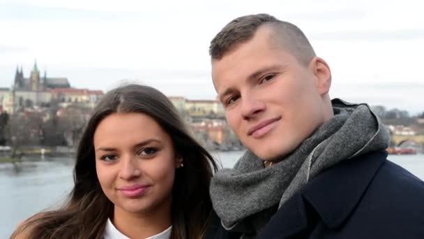 Mladý šťastný pár v lásce polibek a úsměv do kamery - město (Praha) v pozadí - detail