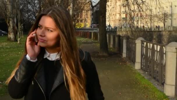 junge attraktive Frau telefoniert und geht in Stadt - Park