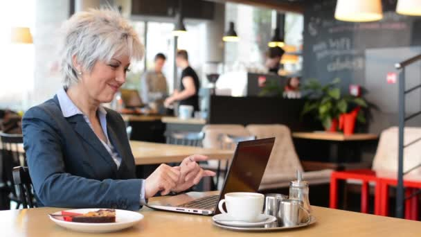 Business middle aged woman works on computer (notebook) in cafe