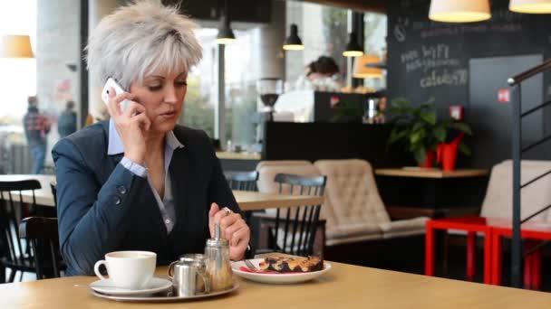 Frau mittleren Alters telefoniert im Café - Kaffee und Kuchen