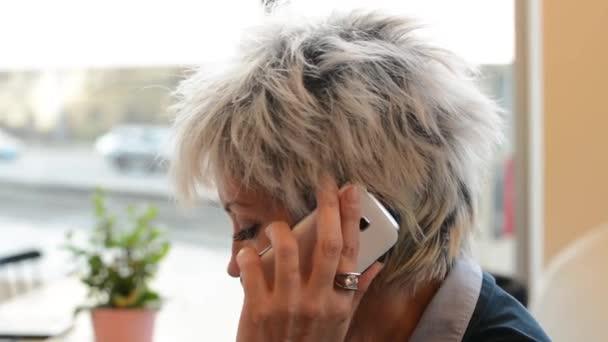 Středního věku žena telefon v café - káva a dort - městské ulice s automobily v pozadí - výstřel ze strany