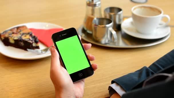La donna lavora sullo schermo smartphone verde in caffè - caffè e torta